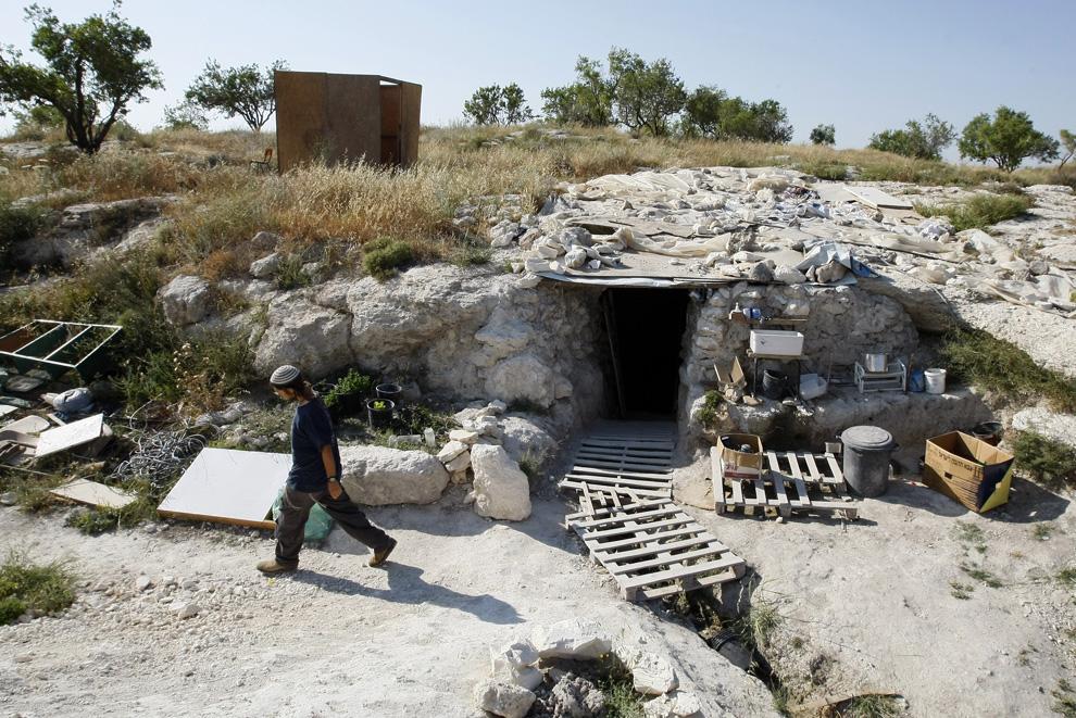Pemukim Yahudi berjalan melewati sebuah gua berubah menjadi tempat penampungan darurat dekat pemukiman Kedumim di pinggiran Nablus di Tepi Barat, 26 Mei 2009.  Sekelompok pemukim percaya bahwa mereka tidak akan dievakuasi dari gua, karena tidak dibangun tempat penampungan.  (Jack GUEZ / AFP / Getty Images)