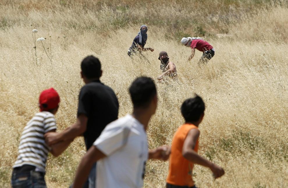 Еврейские поселенцы в масках из поселения Ицхар швыряют камни в палестинцев на окраине деревни Хавара к югу от Наблуса, в северной части Западного берега 1 июня 2009. (MENAHEM KAHANA/AFP/Getty Images)