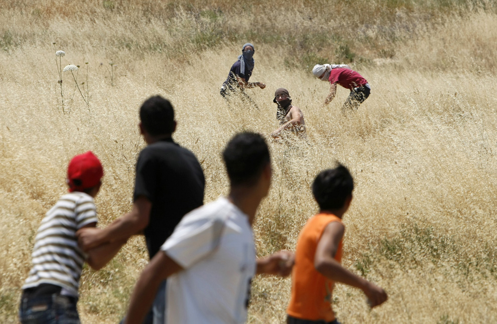 Pemukim Yahudi dari pemukiman Yitzhar masker melemparkan batu ke arah warga Palestina di pinggiran desa Hawara, selatan Nablus di utara Tepi Barat, 1 Juni 2009.  (Menahem Kahana / AFP / Getty Images)