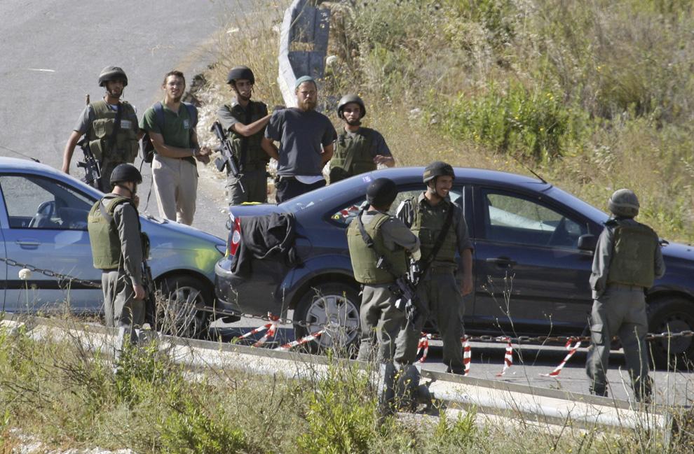 Penjaga perbatasan Israel ditahan pemukim Yahudi dari Yitzhar dekat kota utara Nablus di Tepi Barat pada hari Senin, 1 Juni 2009.  Pada hari ini, banyak pemukim Yahudi di seluruh Tepi Barat utara menyerang pekerja Palestina dan dipentaskan api di protes terhadap penghancuran oleh otoritas Israel pemukiman ilegal.  (AP Photo / Nasser Ishtayeh)