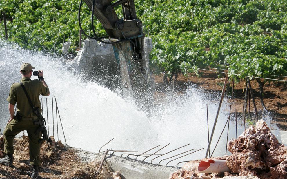 Израильский солдат наблюдает за тем, как бульдозер разрушает канал построенный палестинцем на своей земле недалеко от еврейского поселения Qiryat Arba'a в Хевроне на оккупированных территориях Западного берега 8 июня 2009. Израильские войска арестовали арендодателя и разрушили канал, который был якобы незаконно построен вблизи еврейского поселения. (HAZEM BADER/AFP/Getty Images)