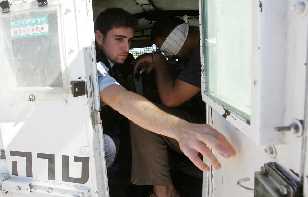 Израильский полицейский закрывает дверь автомобиля, после ареста палестинца за строительство канала вблизи израильского поселения Qiryat Arba'a в Хевроне на оккупированных территориях Западного берега 8 июня 2009. (HAZEM BADER/AFP/Getty Images)