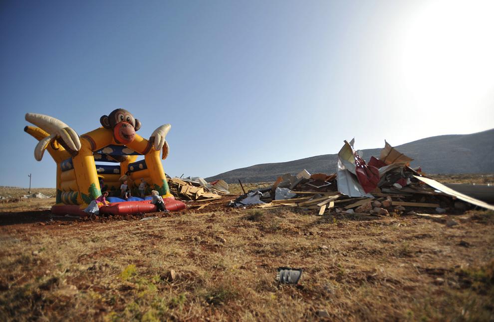 Дети израильских поселенцев играют на надувном аттракционе рядом с развалинами незаконных укреплений Маоц Эстер, неподалеку от поселения Кохав Ха Шахар, к востоку от Рамаллы 4 июня 2009. (YEHUDA RAIZNERAFP/Getty Images)