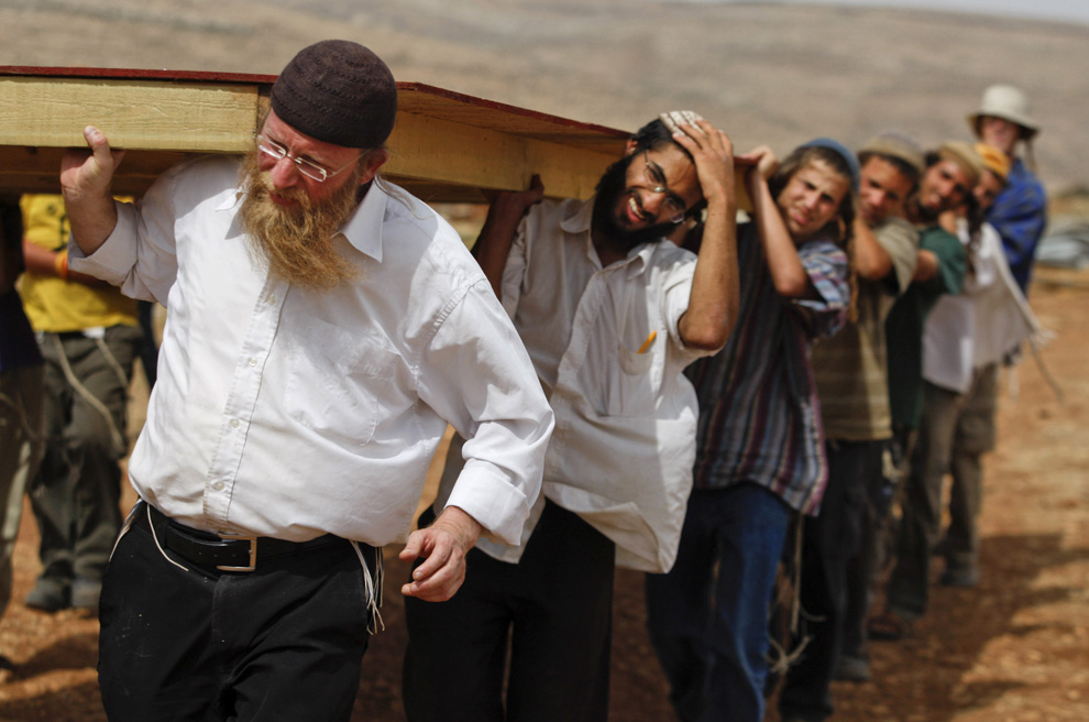 Еврейские поселенцы восстанавливают здание укрепления Маоц Эстер на Западном берегу к северо-востоку от Рамаллы, в четверг, 4 июня 2009. (AP Photo/Dan Balilty)