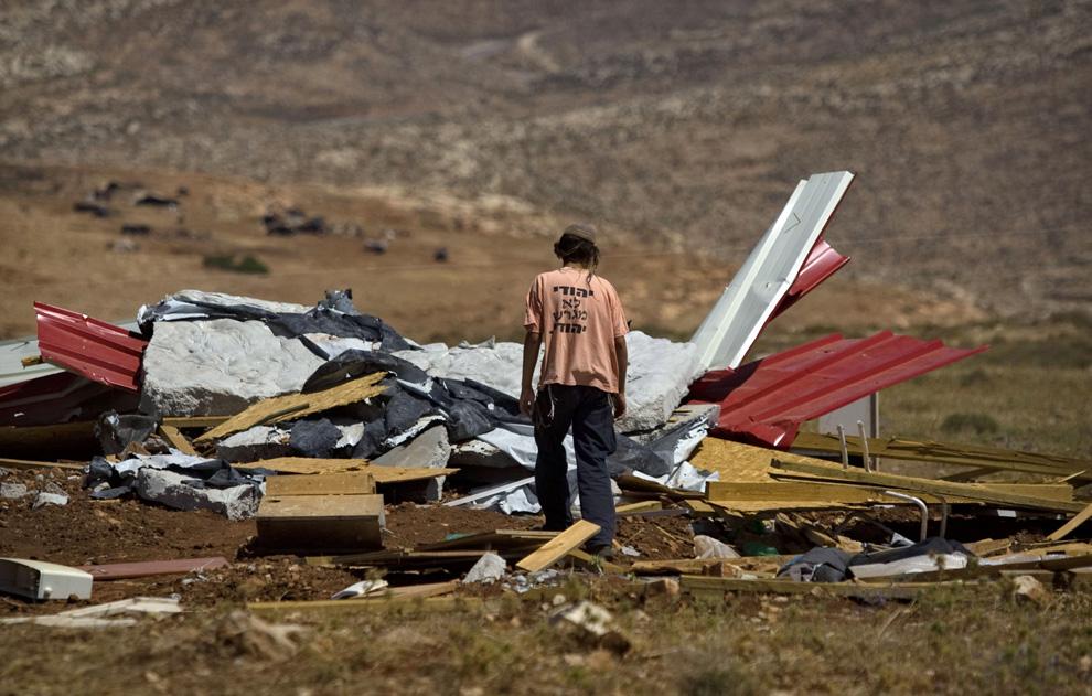 Еврейский поселенец смотрит на развалины укрепления, которое несколько раз за последние недели разрушалось израильскими солдатами и заново отстраивалось еврейскими поселенцами. Фото сделано в на Западном берегу в поселении Маоц Эстер близ Рамаллы, в воскресенье, 7 июня 2009. (AP Photo/Sebastian Scheiner)