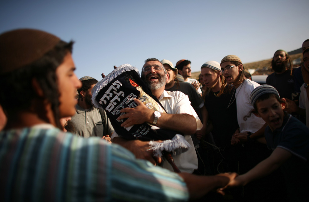 Pemukim Yahudi memeluk sebuah gulungan Taurat selama upacara di Maoz Ester, setelah polisi Israel dihancurkan pada malam memperkuat kedua kalinya.  Gambar diambil 4 Juni 2009 di Maoz Ester, dekat Ramallah, Tepi Barat.  (Uriel Sinai / Getty Images)