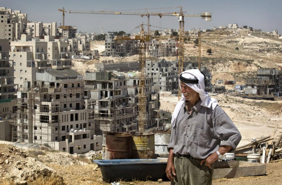Палестинец Саид Эйд стоит рядом со своим домом, (на фото дом не виден), а на фоне – продолжается строительство новой жилищной застройки в окрестностях еврейского поселения Хар-Хома в Восточном Иерусалиме, в среду, 3 июня 2009. (AP Photo/Sebastian Scheiner)