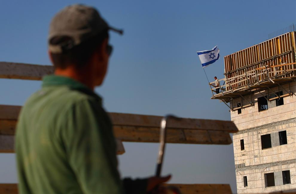 Berdiri di samping bendera Israel dalam mengembangkan malam angin pembangun beristirahat setelah seharian bekerja keras di pembangunan perumahan baru di pemukiman Yahudi Alpha Menashe 8 Juni 2009 di Tepi Barat.  (David Silverman / Getty Images)
