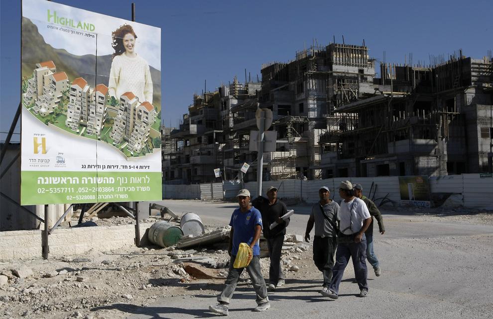 Pekerja Palestina berjalan melewati papan reklame perumahan draft baru di pemukiman Yahudi Maale Adumim di Tepi Barat yang diduduki, 7 Juni 2009.  (Menahem Kahana / AFP / Getty Images)