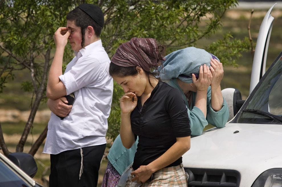 Израильтяне стоят у входа в West Bank в еврейском поселении Bat Ayin на Западном берегу в четверг, 2 апреля 2009. В этот день палестинский боевик, с топором убил в Bat Ayin 13-летнего и ранил 7-летнего израильского мальчика, после чего скрылся. (AP Photo/Sebastian Scheiner)