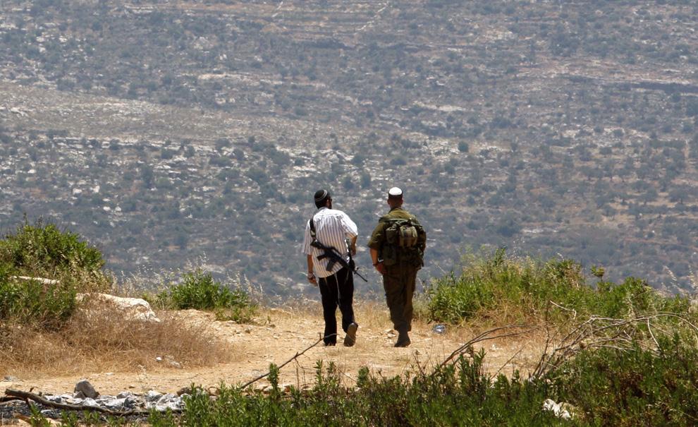 Еврейский поселенец и израильский солдат вместе патрулируют поселение Хорша, расположенное на Западном берегу возле Рамаллы. Фото сделано 14 июня 2009. (REUTERS/Gil Cohen Magen)