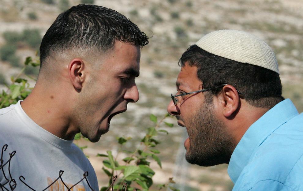 Спор еврейского поселенца и палестинского демонстранта во время демонстрации протеста против незаконного сооружения близ израильского поселения Kharsina на Западном берегу 22 мая 2009. (HAZEM BADER/AFP/Getty Images)