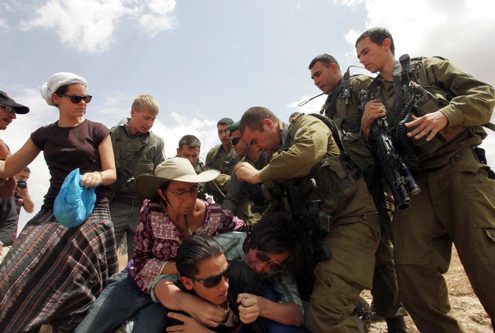 Tentara Israel perkelahian dengan aktivis Palestina dan asing, kampanye perdamaian, yang mendirikan tenda di samping gedung dibangun secara ilegal dari pemukim di tanah milik keluarga Palestina Haddar, dekat desa Yatta di selatan Tepi Barat 6 Juni 2009.  (Hazem Bader / AFP / Getty Images)