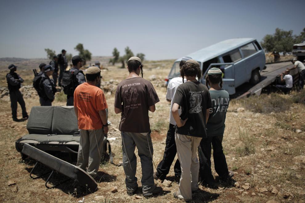Еврейские поселенцы наблюдают за тем, как израильская полиция убирает автомобиль и выполняет приказ разрушить незаконное сооружение близ поселения Мигрон на оккупированном Западном берегу 3 мая 2009. (MARCO LONGARI/AFP/Getty Images)
