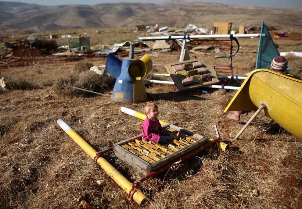 Si kecil duduk di reruntuhan taman bermain di desa Maoz Ester, setelah polisi Israel menghancurkan waktu kedua 3 Juni 2009 di Maoz Ester, sebelah timur Ramallah.  (Uriel Sinai / Getty Images)