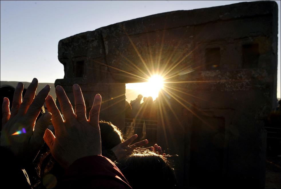 """Тысячи людей поднимают руки к первым лучам """"Тата Инта"""" (Бога Солнца), которые пробиваются через """"Врата от Солнца"""" во время празднования нового года 21 июня, в Тиванаку (или Тиауанако), 71 км на восток от Ла-Пас, Боливия. (AFP/Getty Images/Aizar Raldes)"""