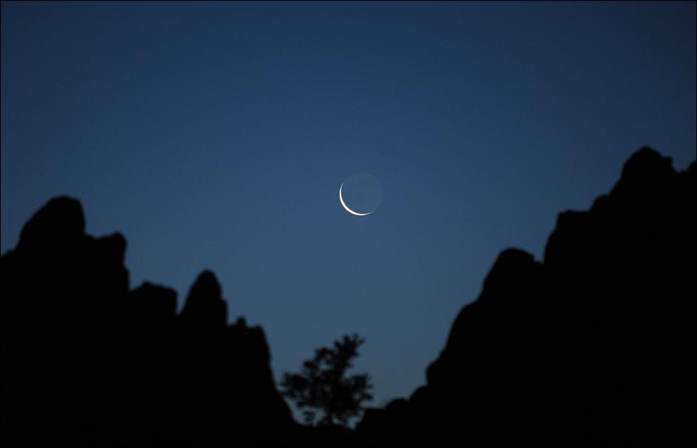 Вскоре после восхода солнца, рано утром 21 июня Луну видно в скалистом гребне мегалитической обсерватории Кокино, на которой существуют многочисленные каменные метки для отслеживания движения солнца и луны. (AFP/Getty Images/ Robert Atanasovski )