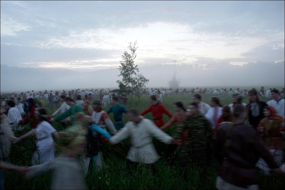 Славянские родноверы (язычники) танцуют вокруг дерева во время празднования летнего солнцестояния под Малоярославцем, рано утром в субботу, 20 июня. (AP/Sergey Ponomarev)