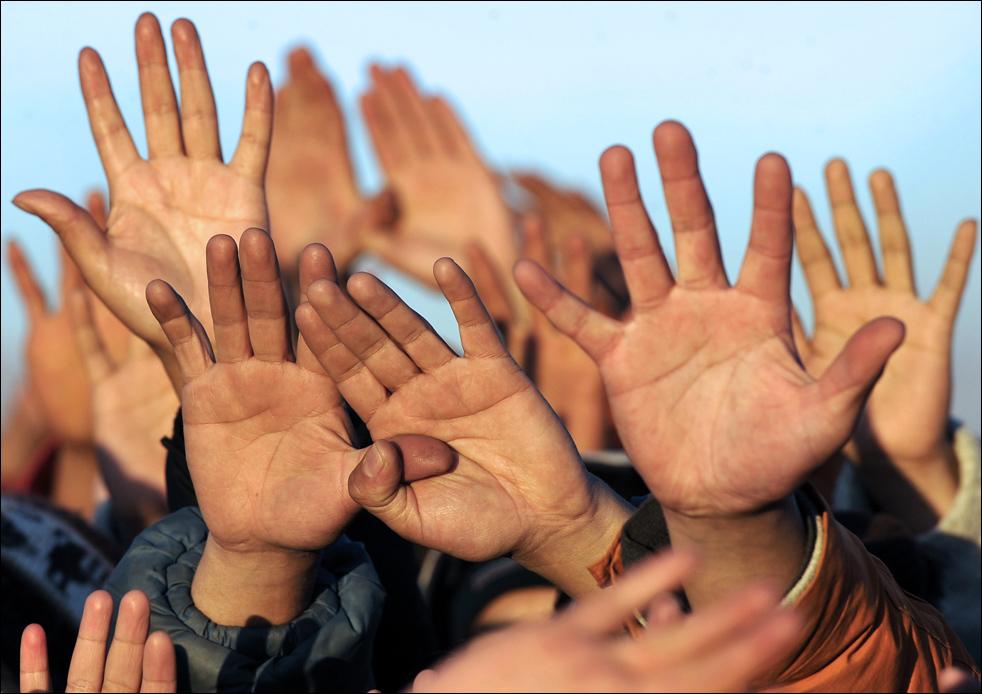 """Тысячи людей поднимают руки к первым лучам """"Тата Инта"""" (Бога Солнца), которые пробиваются через """"Врата от Солнца"""" – каменные ворота в индейском городище Тиауанако, которые, как полагают, использовались в качестве календаря в зимнее солнцестояния аймара во время празднования нового года 21 июня, в Тиванаку (или Тиауанако), 71 км на восток от Ла-Пас, Боливия. Во время встречи года аймара 5517 тут побывали около 30 тысяч человек. (AFP/Getty Images/Aizar Raldes"""