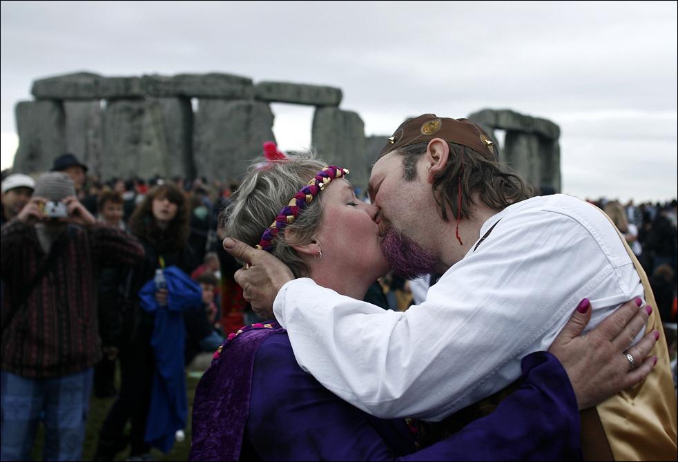 Карл Клинкенборг и его жена Gigha целуются во время своей свадебной церемонии, которая прошла во время празднования летнего солнцестояния в Стоунхендже в западной Англии, в начале воскресенье, 21 июня. Свадебные приметы гласят, что жениться в начале лета - добрый знак. (AP/Akira Suemori)