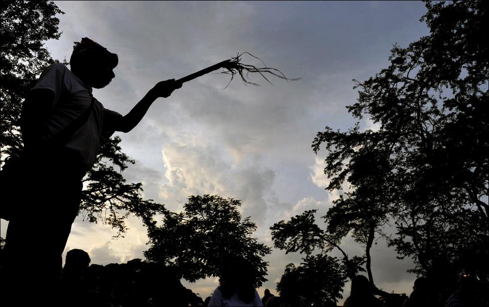 """Целитель проводит ритуал на празднике """"Инти Райми"""" (Праздник солнца), 21 июня, в Кали, департамент Валье-дель-Каука, Колумбия. Этот праздник - старинный ритуал Инков поклонения солнцу, главному богу Инков. Это знак наступления венца года инков и скорого сбора урожая, который, если того пожелают боги, окажется обильным. (AFP/Getty Images/Luis Robayo)"""