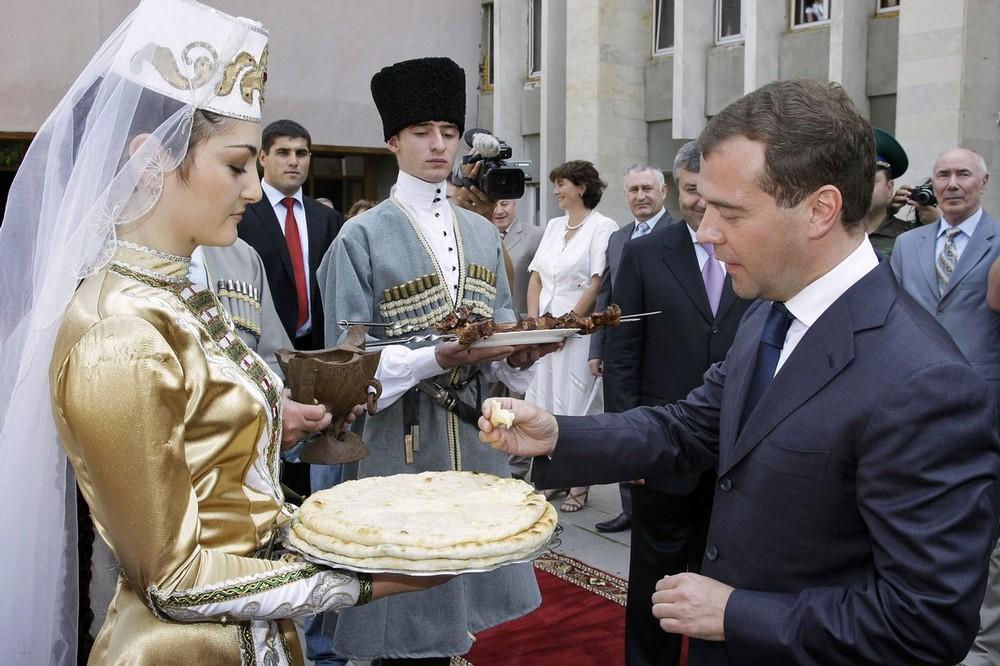) Президент России Дмитрий Медведев пробует традиционные осетинские лепешки во время визита в Цхинвали 13 июля 2009 года в Южной Осетии. (VLADIMIR RODIONOV/AFP/Getty Images)