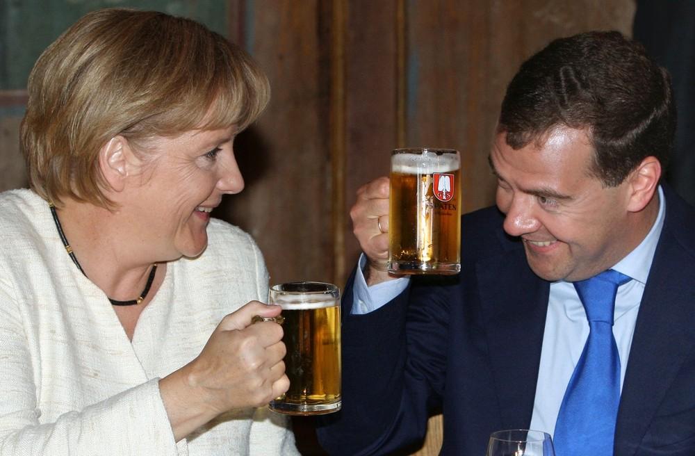 ) На снимке, сделанном 16 июля 2009, немецкий канцлер Ангела Меркель и президент России Дмитрий Медведев чокаются бокалами с пивом в Мюнхене. Руководителям стран подали обед из трех блюд. На столе был паштет из лосося, баварские куриные грудки с белыми грибами и гарниром из шпината и картофеля, а также блинчики с ягодами и соус с кардамоном. (MIKHAIL KLIMENTYEV/AFP/Getty Images)