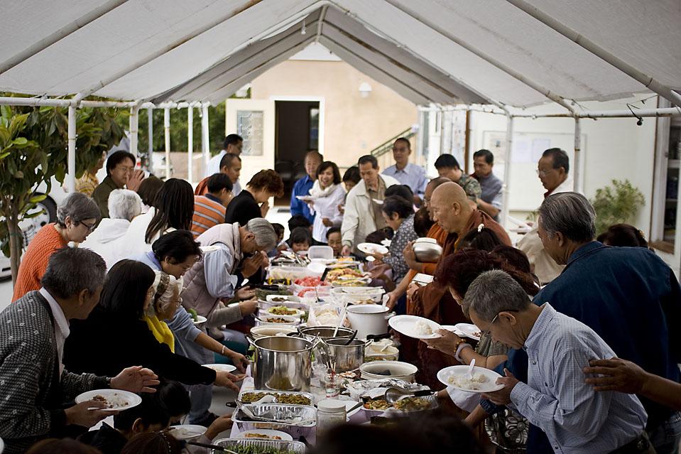 Члены сообщества приносят еду г-ну Джомтонгу и двум другим монахам. Их пожертвования обеспечивают содержание всего комплекса, который включает в себя пруд с лилиями и малыми мостами, построенными г-ном Джомтонгом, а также цветы, которые он посадил. На снимке – трапеза в храме. (Michal Czerwonka for The Wall Street Journal)