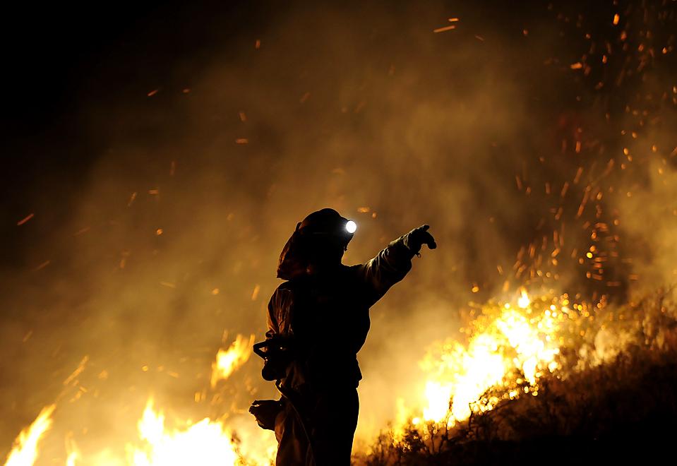 1) Пожарный находится рядом с огнем во время лесного пожара в Андорре. Около 500 человек боролись с огнем, который раздувал ветер. Четверо пожарных погибли. (Pedro Armestre/Agence France-Presse/Getty Images)