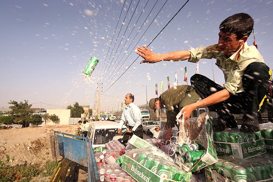 7) Полиция опустошает банки конфискованного пива в столице Ирана, Тегеран. Хранение, производство и употребление алкоголя категорически запрещено в это исламской республике. (Farzin Nemati/Agence France-Presse/Getty Images)