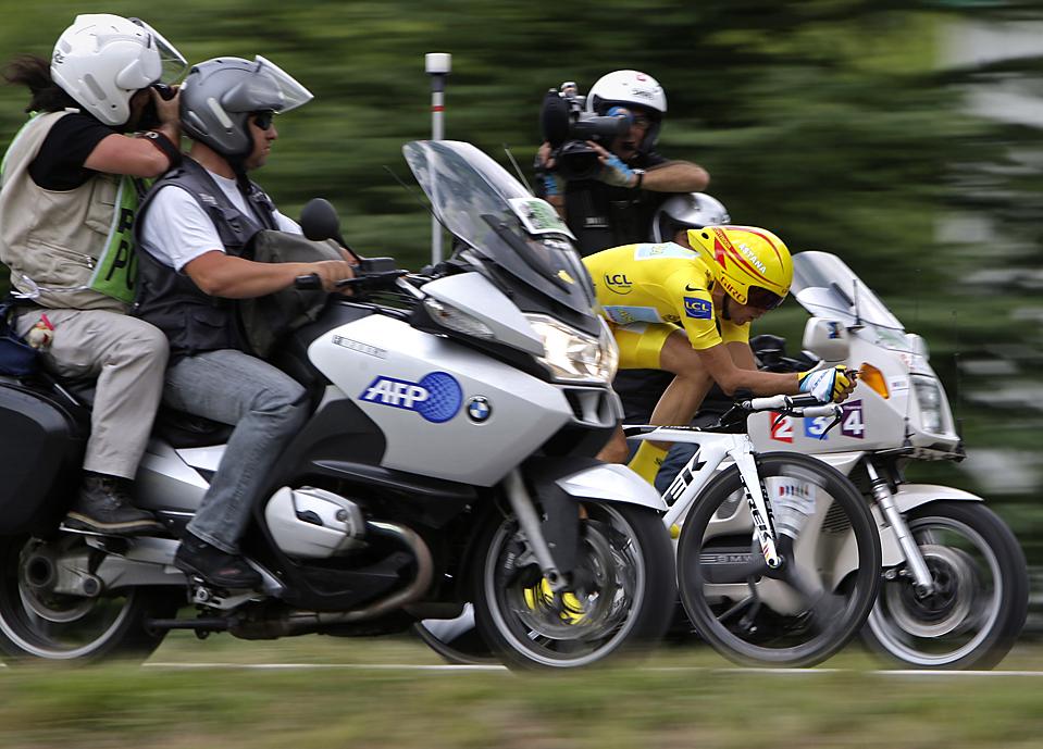 """8) Испанец Альберто Контрадор в желтой майке победителя едет между фотокорреспондентами к финишу 18-го этапа """"Тур де Франс"""" в Аннеси, Франция. Альберто пришел первым в этом этапе велогонки. Между тем, Лэнс Армстронг заявил, что в 2010 году планирует в партнерстве с RadioShack сформировать команду, базирующуюся в США. (Bas Czerwinski/Associated Press)"""