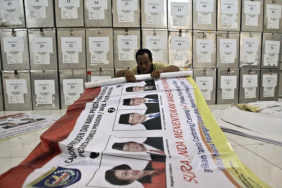 2) В столице Индонезии Джакарте работник на фоне избирательных урн скручивает плакат с портретами кандидатов в президенты. Индонезия проводит президентские выборы сегодня, в среду. (Irwin Fedriansyah/Associated Press)