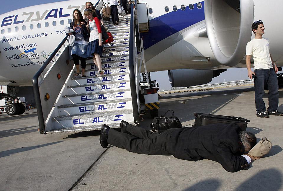 5) Еврейский путешественник из Северной Америки целует землю после высадки из пассажирского реактивного самолета Эль-Аль на Международном аэропорту Бен-Гуриона недалеко от Тель-Авива. (Gil Cohen/Reuters)