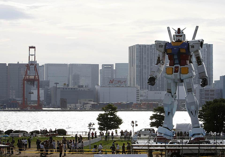 """7) Посетители токийского парка смотрят на 18-метровую фигуру робота """"Gundam"""", одного из героев популярных японских аниме сериалов. Эта модель была построена в честь 30-й годовщины с момента появления первого сериала об это роботе. (Kim Kyung-Hoon/Reuters)"""