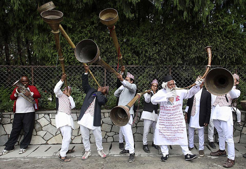 """8) Сторонники бывшего непальского короля Гьянендры играют народную музыку, у личной резиденции короля в Катманду, чтобы поздравить его с днем рождения. Прошел уже год со времени свержения монархии, и бывший король Непала заявил, что он """"очень возмущен"""" отсутствием прогресса в установлении мира и процветания для народа Гималайского нации. (Gopal Chitrakar/Reuters)"""