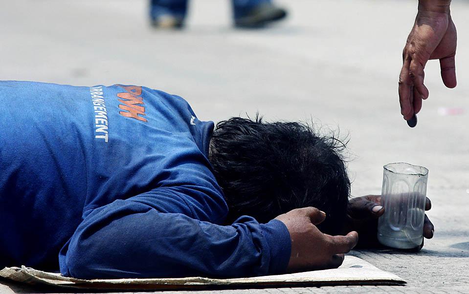 9) Прохожий подает милостыню нищему на улице в Маниле. В этом году в Филиппинах пять миллионов бедных семей будут получать государственные денежные пособия и медицинское страхование. В этом году в общей сложности 321 тыс. семей – а это число в два раза превысило запланированное - имеют право на получение денежного пособия в размере до 9.000 песо, что равняется $ 187,50. (Junie Doctor/ AFP/Getty Images)