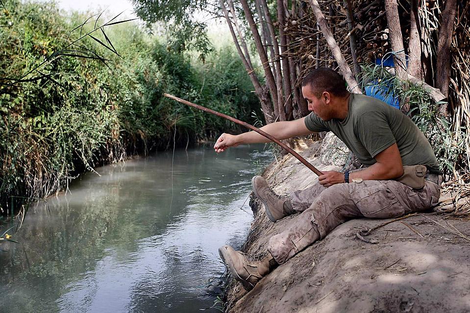 """11) Капрал морской пехоты Тали Рамирес из города Сейнт Пол, штат Миннесота на досуге ловит рыбу в канале афганского города Миан Поштех. Морская пехота находится в этом районе в рамках операции Khanjari, направленной на установление контроля в областях, используемой боевиками движения """"Талибан"""" для пополнения маршрутов. (Joe Raedle / Getty Images)"""