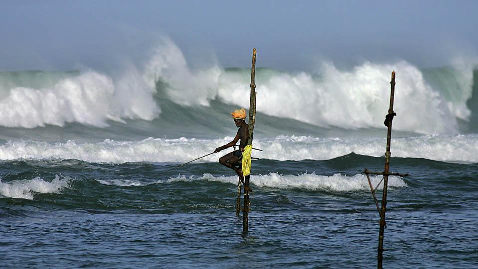 16) Шри-ланкийский рыбак стоит на специальной тонкой свае воткнутой в океанское дно. Снимок сделан в регионе Коггала, на юг от ланкийского города Галле. Шри-Ланка. (Gurinder Osan/Associated Press)
