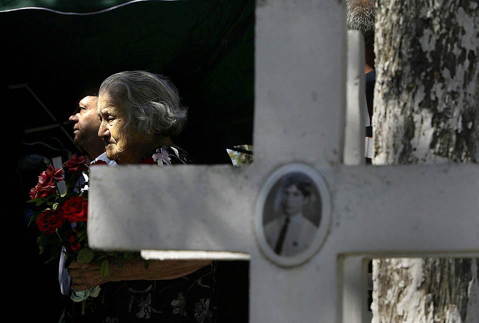 Женщина с розами в Никосии на Кипре у могил киприотских солдат, которые погибли 15 июля 1974 года во время свержения Архиепископа Макариоса III. (Petros Karadjias/Associated Press)