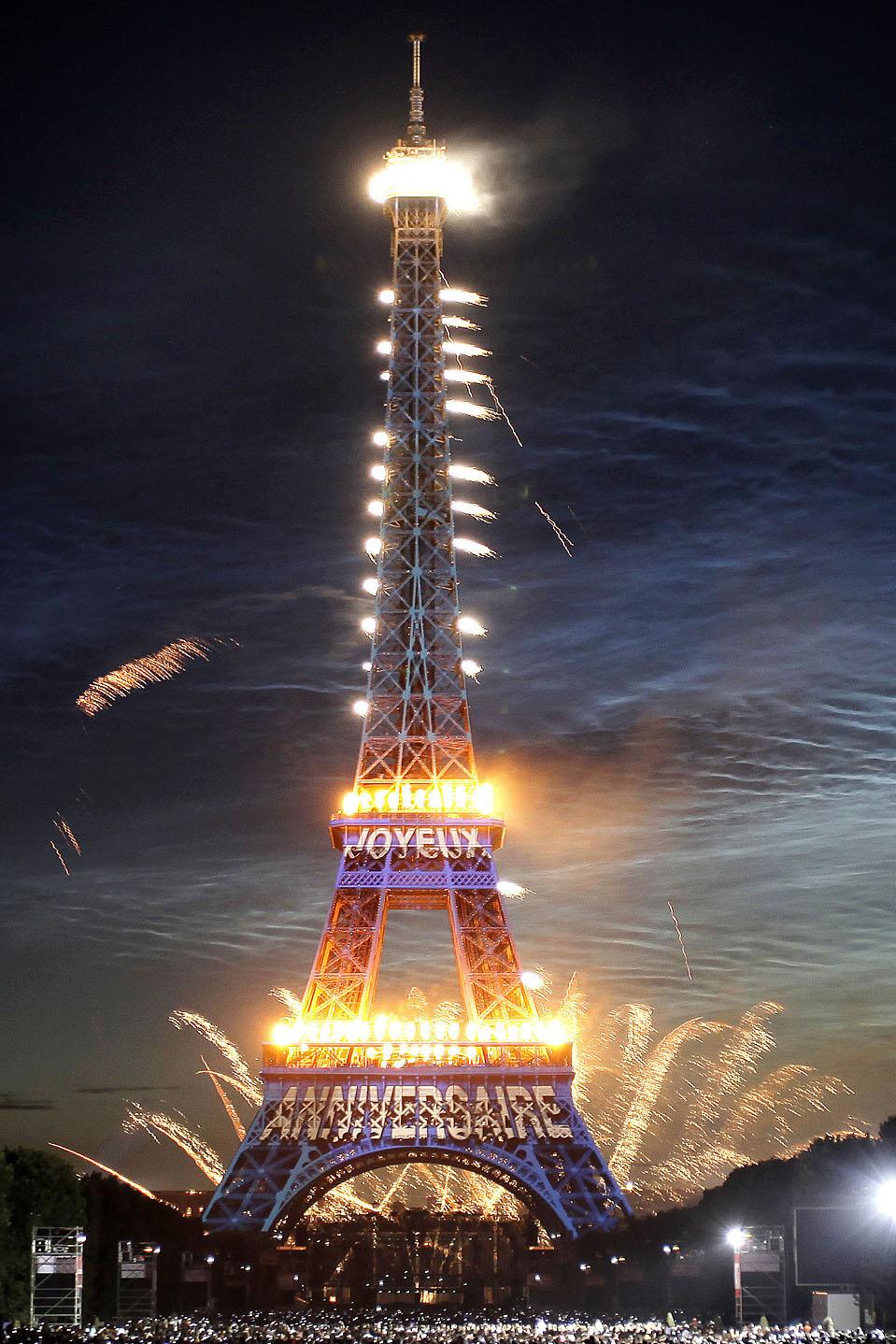 Фейерверк над Эйфелевой башней в Париже во время празднования дня взятия Бастилии. Надпись на башне «С днем рожденья» (Thibault Camus/Associated Press)