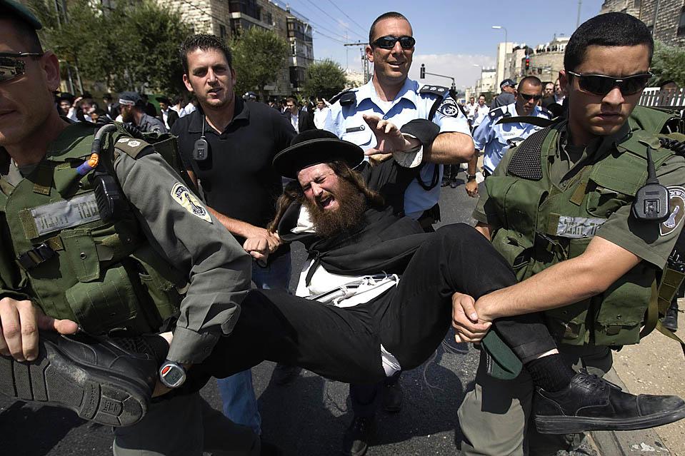 Израильская полиция задержала ультра-ортодоксального еврея в Иерусалиме во время акции протеста против ареста ультра-ортодоксальной женщины, которая, как утверждается, дурно обращалась со своим сыном. (Baz Ratner/Reuters)