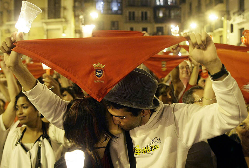 Участники фестиваля Сан Фермин в испанском городе Памполона целуются со свечами и традиционным красным платком в руках во время церемонии закрытия 9-дневного праздника. В этом году во время забега с быками один человек погиб, а 2 попали в реанимацию. (Susana Vera/Reuters)