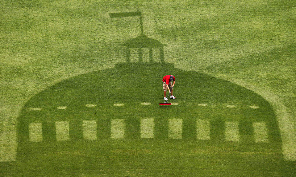 Рабочий ухаживает за газоном на стадионе Буша перед предстоящей игрой звезд бейсбола в Сент-Луисе. На поле видна тень от старого здания суда. (Charlie Riedel/Associated Press)