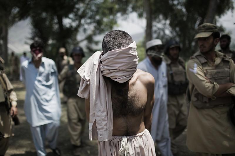 """5) Мужчин, подозреваемых в принадлежности к движению """"Талибан"""", ведут на допрос, после того, как они были захвачены пакистанскими военными во время облавы в пакистанском городе Дагар. (Daniel Berehulak/Getty Images)"""