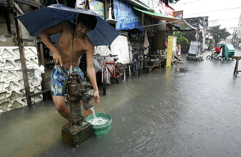 6) Житель филиппинского города Макати набирает воду у колонки на затопленной улице, после того, как из-за тропических ливней были затоплены некоторые регионы в Маниле и прилегающих областях. (Aaron Favilia/Associated Press)