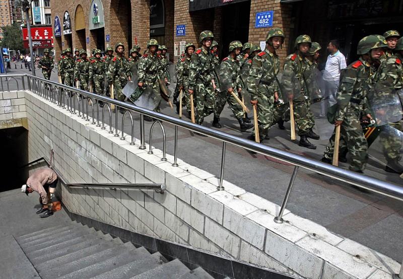 9) Уйгурец пристегивает свой протез, в то время как патруль китайской военизированной полиции идет по улице Урумчи. После кровавых этнических столкновений на прошлой неделе, в которых, как сообщают официальные источники, погибло почти 200 человек, Китай продолжает соблюдать суровые меры по обеспечению безопасности. (Elizabeth Dalziel/Associated Press)