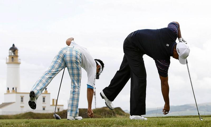 10) Тайгер Вудс из США, справа, и Рио Исикава из Японии готовятся к удару на девятой лунке на поле для игры в гольф Тернберри в Шотландии, в первом раунде британского Открытого чемпионата. (Jon Super/Associated Press)