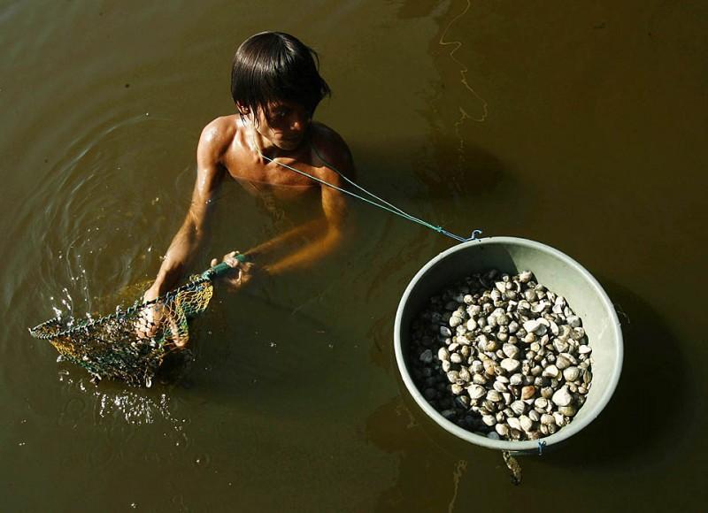 15) Даенг Кулли собирает ракушки для продажи на пляже Лосари в индонезийском городе Макассар, в провинции Южный Сулавеси. (Yusuf Ahmad/Reuters)