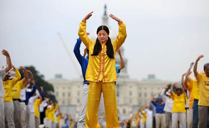 13) Сотни последователей учения Фалуньгун (нового религиозного движения, возникшего в КНР на основе традиционной китайской гимнастики цигун в начале 1990-х годов) занимаются медитацией посредством телодвижений в Вашингтонском Национальном Парке, чтобы отметить 10-летнюю годовщину запрета на эту религиозную практику в Китае. (Tim Sloan/Agence France-Presse/Getty Images)