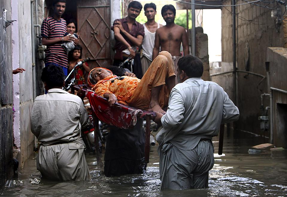 ) Люди выносят женщину из ее дома во время наводнения, вызванного обильными осадками в Карачи, Пакистан. Как сообщают официальные источники, в результате наводнения погибли, по меньшей мере, 26 человек. Из-за дождей отрезано электричество и затоплены основные дороги. (Fareed Khan/Associated Press)